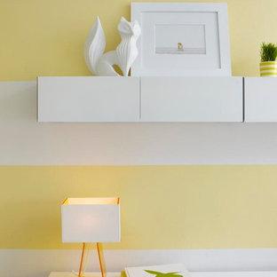 Idée de décoration pour une chambre de bébé neutre design avec un sol en bois brun, un sol marron et un mur jaune.