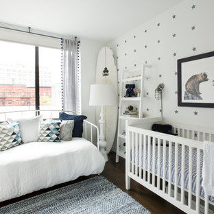 This is an example of a beach style gender-neutral nursery in New York with multi-coloured walls and dark hardwood floors.