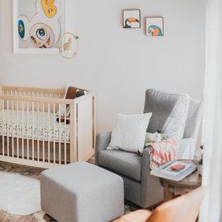 Idées déco pour une chambre de bébé neutre éclectique de taille moyenne avec un mur blanc et un sol en bois brun.
