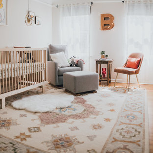 This is an example of a medium sized eclectic gender neutral nursery in Los Angeles with white walls and medium hardwood flooring.