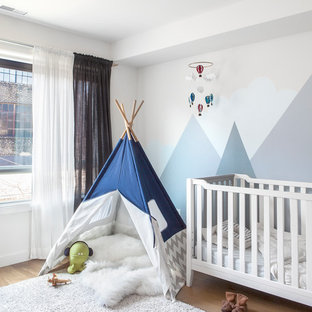 This is an example of a traditional gender neutral nursery in Toronto with multi-coloured walls, light hardwood flooring and beige floors.