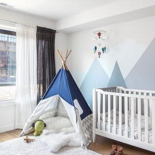 Foto de habitación de bebé neutra clásica renovada con paredes multicolor, suelo de madera clara y suelo beige