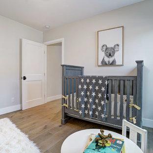 Modelo de habitación de bebé niño de estilo de casa de campo con paredes beige, suelo de madera en tonos medios y suelo marrón