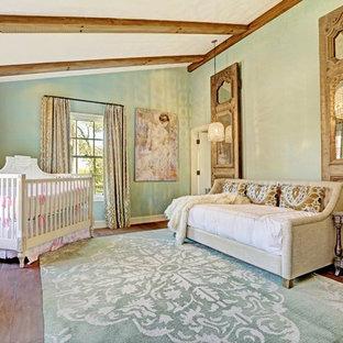 Réalisation d'une très grand chambre de bébé neutre tradition avec un mur vert et un sol en bois brun.