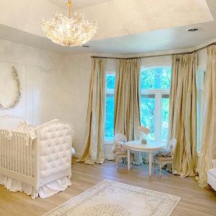 Réalisation d'une chambre de bébé fille avec un mur blanc, un sol en bois clair et un plafond décaissé.