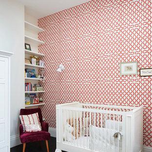 Inredning av ett modernt könsneutralt babyrum, med flerfärgade väggar och svart golv