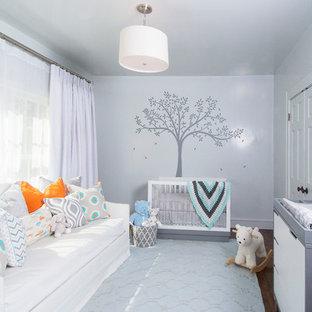 Imagen de habitación de bebé neutra tradicional renovada, de tamaño medio, con paredes grises y suelo de madera oscura