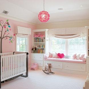 ニューヨークの広いトランジショナルスタイルのおしゃれな赤ちゃん部屋 (ピンクの壁、カーペット敷き、女の子用、ベージュの床) の写真