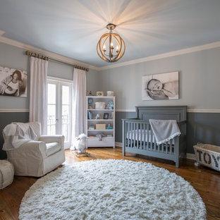 Diseño de habitación de bebé neutra tradicional renovada con paredes grises y suelo de madera en tonos medios