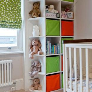Modelo de habitación de bebé neutra ecléctica, pequeña, con paredes beige, moqueta y suelo beige