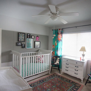 This is an example of a small bohemian nursery for girls in San Diego with grey walls and carpet.