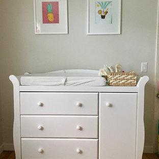 Imagen de habitación de bebé niña moderna, pequeña, con paredes grises