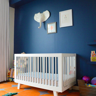 This is an example of a medium sized bohemian nursery for girls in New York with blue walls and medium hardwood flooring.
