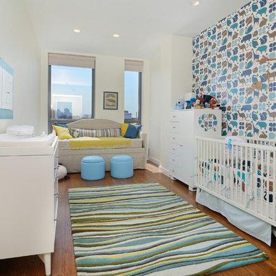 Mid-sized trendy boy medium tone wood floor nursery photo in New York with multicolored walls