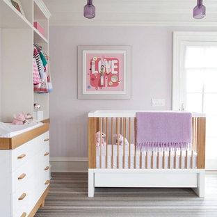 Ejemplo de habitación de bebé niña tradicional renovada con paredes púrpuras, moqueta y suelo gris