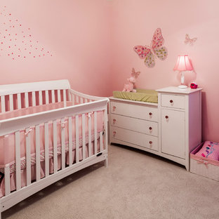 This is an example of a nursery for girls in Baltimore with pink walls and carpet.