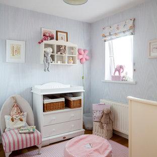 Ejemplo de habitación de bebé neutra clásica con paredes azules y suelo de madera en tonos medios