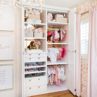 Inspiration for a mid-sized timeless girl medium tone wood floor nursery remodel in Los Angeles with white walls