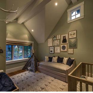 Esempio di una cameretta per neonati neutra rustica di medie dimensioni con pareti verdi, pavimento in legno massello medio e pavimento marrone