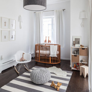 This is an example of a medium sized traditional gender neutral nursery in New York with white walls and dark hardwood flooring.