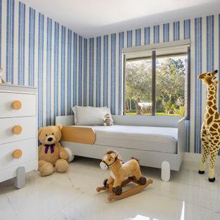 Idée de décoration pour une grand chambre de bébé garçon design avec un mur bleu, un sol en marbre et un sol blanc.