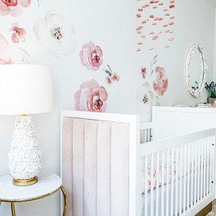 Modelo de habitación de bebé niña clásica renovada, de tamaño medio, con paredes blancas, suelo de bambú y suelo marrón