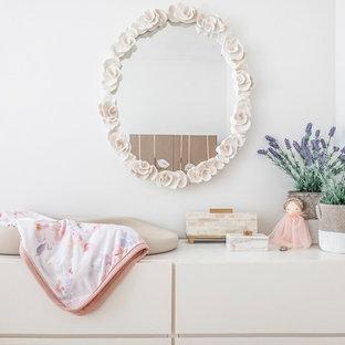 Ejemplo de habitación de bebé niña clásica renovada, de tamaño medio, con paredes blancas, suelo de bambú y suelo marrón