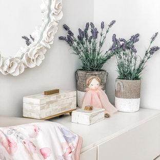 Aménagement d'une chambre de bébé fille classique de taille moyenne avec un mur blanc, un sol en bambou et un sol marron.