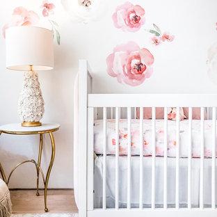 Inspiration pour une chambre de bébé fille traditionnelle de taille moyenne avec un mur blanc, un sol en bambou et un sol marron.
