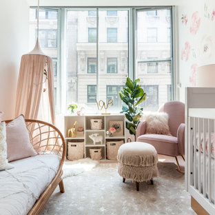 Medium sized traditional nursery for girls in New York with white walls, bamboo flooring and brown floors.