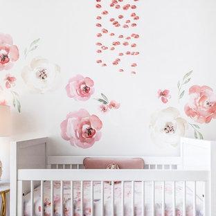 Idée de décoration pour une chambre de bébé fille tradition de taille moyenne avec un mur blanc, un sol en bambou et un sol marron.