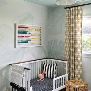 Diseño de habitación de bebé niña costera, de tamaño medio, con paredes verdes, suelo de madera oscura y suelo marrón