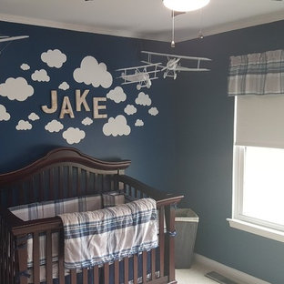 Example of a mid-sized classic boy carpeted and beige floor nursery design in Cincinnati with blue walls