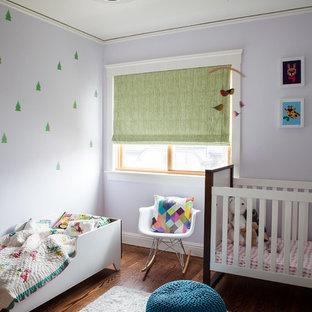 Exemple d'une chambre de bébé fille tendance de taille moyenne avec un mur violet et un sol en bois foncé.