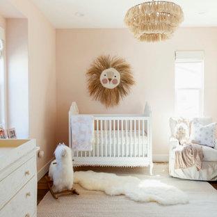 Diseño de habitación de bebé niña tradicional renovada con paredes rosas, suelo de madera oscura y suelo marrón
