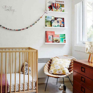 This is an example of a transitional nursery in Melbourne with white walls and grey floor.