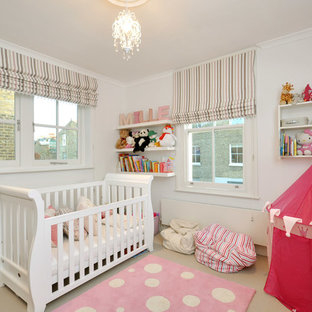 Photo of a classic nursery for girls in London with white walls and carpet.