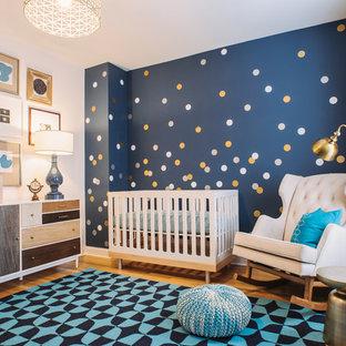 Imagen de habitación de bebé niño tradicional renovada, de tamaño medio, con paredes azules y suelo de madera clara