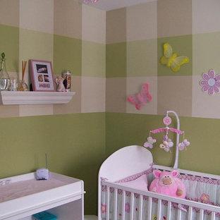 Ispirazione per una piccola cameretta per neonata shabby-chic style con pareti verdi e pavimento in laminato