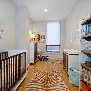 Modelo de habitación de bebé neutra contemporánea con paredes grises, suelo de madera en tonos medios y suelo naranja