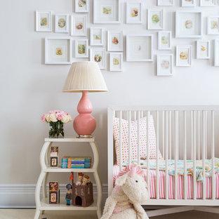 Idées déco pour une chambre de bébé fille classique avec un mur beige, un sol en bois clair et un sol blanc.
