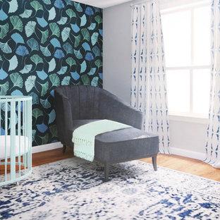 Aménagement d'une petit chambre de bébé neutre contemporaine avec un mur bleu, un sol en bois brun et du papier peint.