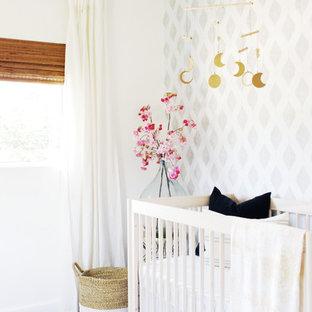 Cette image montre une chambre de bébé neutre traditionnelle avec sol en stratifié, un sol marron et un mur gris.