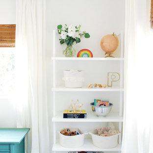 Imagen de habitación de bebé clásica renovada con suelo laminado y suelo marrón