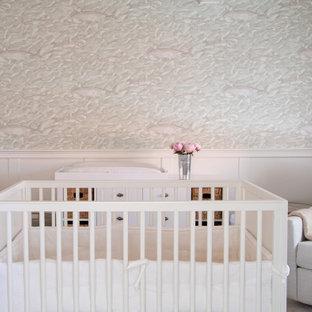 Cette photo montre une chambre de bébé neutre chic de taille moyenne avec un mur blanc, un sol en bois clair, un sol beige, un plafond en poutres apparentes et boiseries.