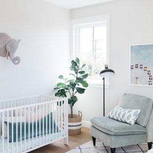 Nursery - farmhouse gender-neutral medium tone wood floor and brown floor nursery idea in Los Angeles with gray walls