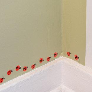 Ispirazione per una cameretta per neonati neutra tradizionale di medie dimensioni con pareti verdi, pavimento in legno massello medio e pavimento grigio
