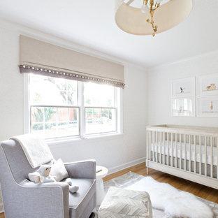 Diseño de habitación de bebé neutra tradicional renovada, de tamaño medio, con paredes grises, suelo de madera clara y suelo gris