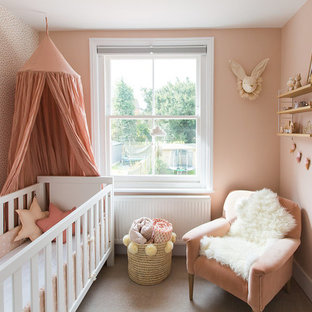 Inspiration for a small scandi nursery for girls in Surrey with pink walls, carpet and beige floors.