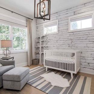 Diseño de habitación de bebé neutra costera, grande, con suelo de madera clara, paredes blancas y suelo beige